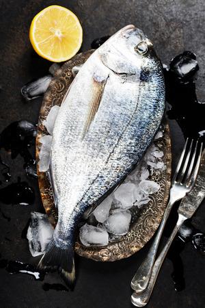 saltwater fish: Fresh fish on ice (dark vintage background)