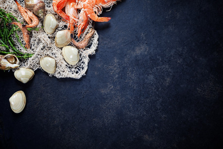 Délicieux poissons frais et fruits de mer sur fond foncé vintage. Poissons, palourdes et crevettes aux herbes aromatiques, des épices et des légumes - des aliments sains, l'alimentation ou concept de cuisine