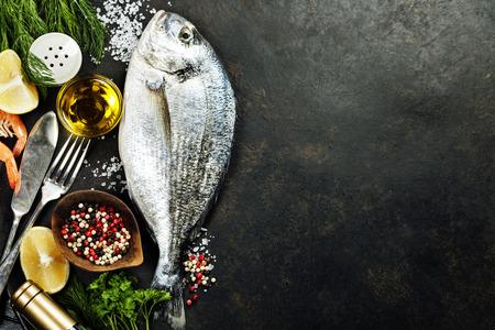 Delicioso pescado fresco en el fondo oscuro de la vendimia. Pescado con hierbas aromáticas, especias y verduras - comida sana, dieta o concepto de cocina Foto de archivo