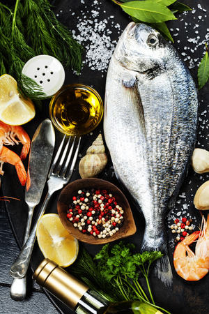 fish oil: Delicious fresh fish and seafood on dark vintage background. Fish, cockles and  shrimps with aromatic herbs, spices and vegetables - healthy food, diet or cooking concept Stock Photo