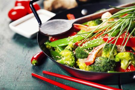 Cozinha chinesa. Stir fry coloridos em uma wok. Camarões com vegetais