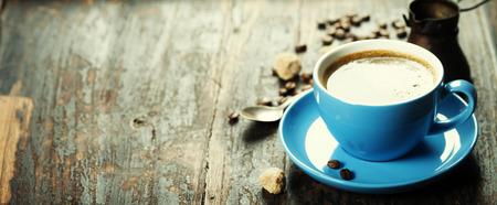 ヴィンテージの木製の背景に青いコーヒー カップ 写真素材