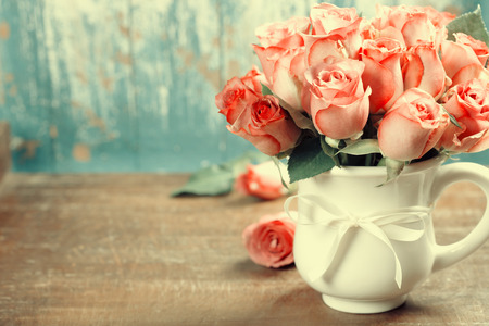 Pink roses in a pot on blue background photo