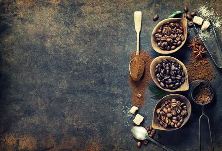 planta de cafe: Vista superior de tres diferentes variedades de granos de café sobre un fondo oscuro de la vendimia