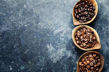 coffeetree: Top view of three different varieties of coffee beans on dark vintage background