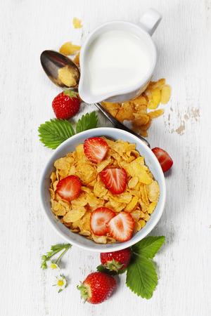 Petit déjeuner sain avec des flocons de maïs, le lait et les fraises sur le vieux fond en bois. concept de la santé et de l'alimentation