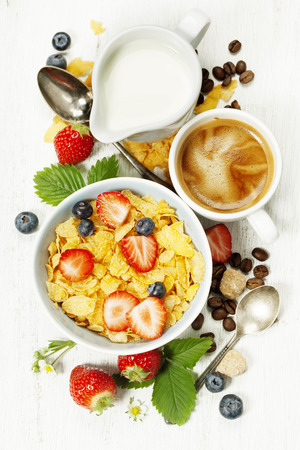 breakfast: Desayuno saludable con café, copos de maíz, leche y bayas en fondo de madera vieja. Salud y concepto de la dieta Foto de archivo
