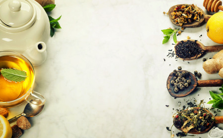 Assortment of dry tea in spoons on marble background