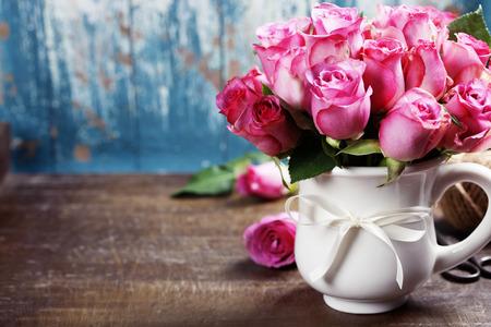 Rosas de color rosa en una olla sobre fondo azul Foto de archivo
