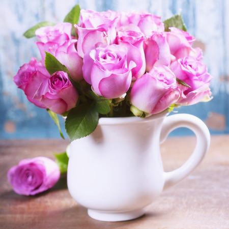 rosas rosadas: Rosas de color rosa en una olla sobre fondo azul Foto de archivo