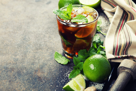 summer drink: Ingredients for making mojitos (ice cubes, mint leaves, sugar and lime on rustic background)