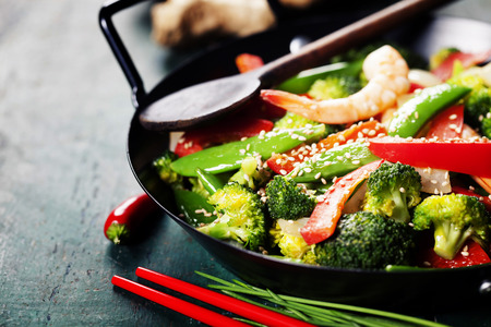 Chinese cuisine. Colorful stir fry in a wok. Shrimps with vegetables 스톡 콘텐츠