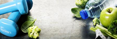 Las verduras frescas saludables, agua y cinta métrica. Salud, deporte y el concepto de dieta Foto de archivo