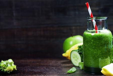 ほうれん草、キュウリ、パセリ、セロリ、レモンの木製の背景を持つ新鮮な有機緑のスムージー 写真素材