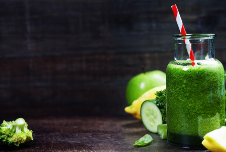 detox: Fresh organic green smoothie with spinach, cucumber, parsley, celery and lemon on wooden background Stock Photo