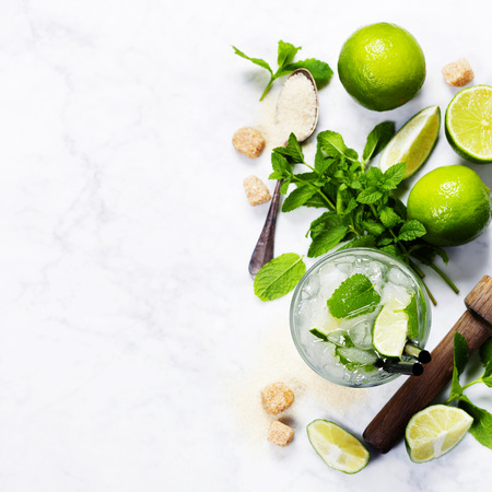 limes: Ingredients for making mojitos (ice cubes, mint leaves, sugar and lime on rustic background)