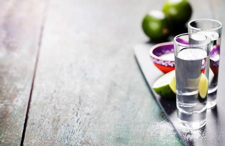 De schoten van Tequila met kalk en zout op rustieke achtergrond Stockfoto