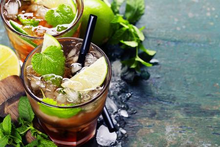 Ingrédients pour faire mojitos (des cubes de glace, feuilles de menthe, sucre et citron vert sur fond rustique)