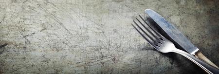 cuchillo de cocina: Tenedor comedor y un cuchillo en la cosecha de fondo rústico con copyspace Foto de archivo