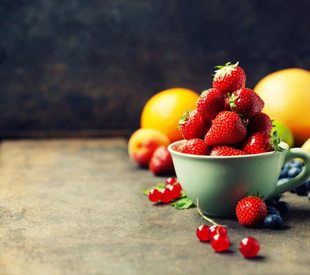 fresa: Fresas en una taza y frutas frescas en el fondo rústico