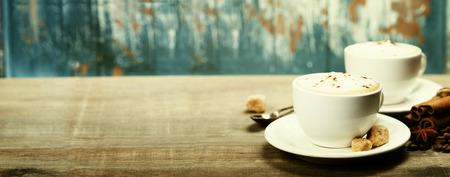 Dos tazas de café en tabla de madera