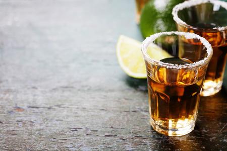 tomando alcohol: Disparos Tequila con limón y sal en el fondo rústico