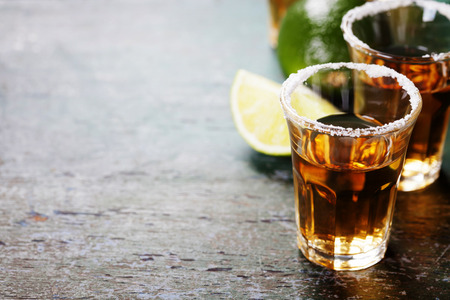 alcoholic drink: Tequila shots with lime and salt on rustic  background
