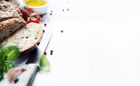 Помидор, хлеб, базилик и оливковое масло на белом мраморном фоне. Итальянская кухня, здоровое питание или вегетарианские концепция Фото со стока