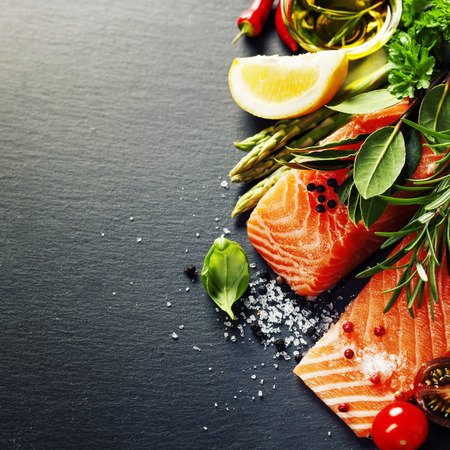 food healthy: Delicious  portion of fresh salmon fillet  with aromatic herbs, spices and vegetables - healthy food, diet or cooking concept Stock Photo