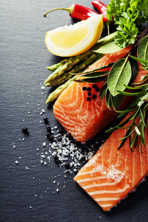 delicious food: Delicious  portion of fresh salmon fillet  with aromatic herbs, spices and vegetables - healthy food, diet or cooking concept Stock Photo