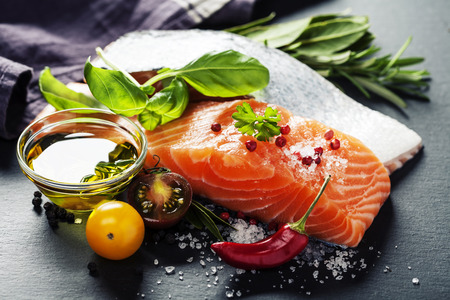 Delicious  portion of fresh salmon fillet  with aromatic herbs, spices and vegetables - healthy food, diet or cooking concept 免版税图像