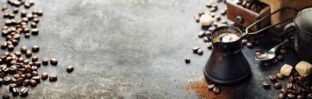 Crisol viejo del café y el molino en fondo rústico oscuro