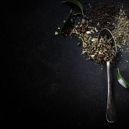 Composición del té con el viejo cuchara en el fondo oscuro