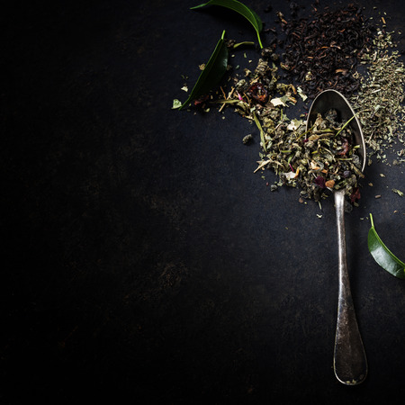 Tea composition with old spoon on dark background Imagens
