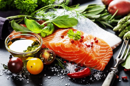 cocina saludable: Delicious  portion of fresh salmon fillet  with aromatic herbs, spices and vegetables - healthy food, diet or cooking concept Foto de archivo