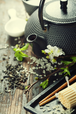 tea table: Chinese Tea Set,chopsticks and sakura branch on rustic wooden table