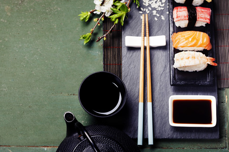 japanese background: Asian food background (black iron tea set and sushi on rustic table) Stock Photo