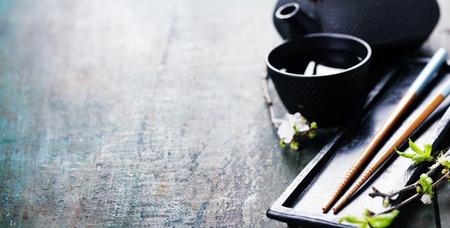 comida japonesa: Conjunto de té chino, palillos y la ramificación de sakura en la mesa de madera rústica