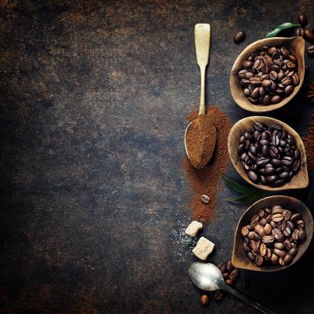 frijoles: Vista superior de tres diferentes variedades de granos de café sobre un fondo oscuro de la vendimia