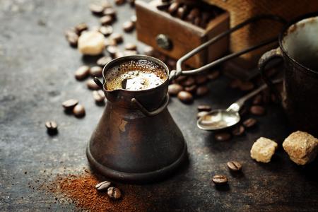 tomando café: Crisol viejo del café y el molino en fondo rústico oscuro