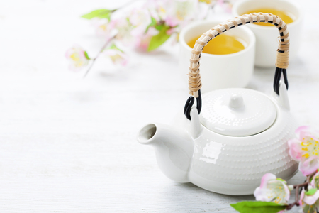 Chinese Tea Set  and sakura branch on bamboo mat Фото со стока