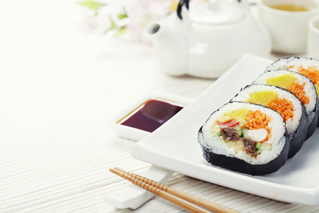 Sushi set, green tea and sakura branch on bamboo mat 스톡 콘텐츠