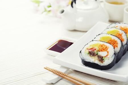 sushi menu: Sushi set, green tea and sakura branch on bamboo mat Stock Photo