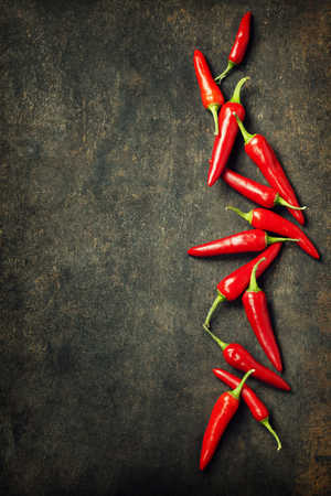 Vibrant red mexican hot chilli pepper on old background