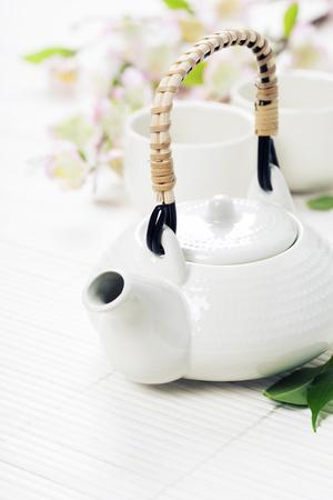 Chinese Tea Set  and sakura branch on bamboo mat Banco de Imagens