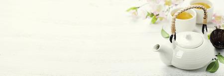 Jogo de chá chinês e ramo de sakura na esteira de bambu
