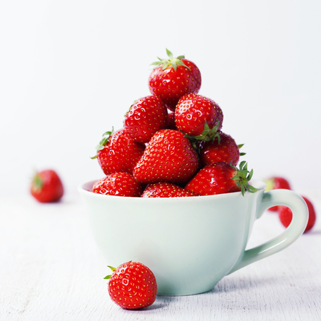 Strawberries in cup on rustic background