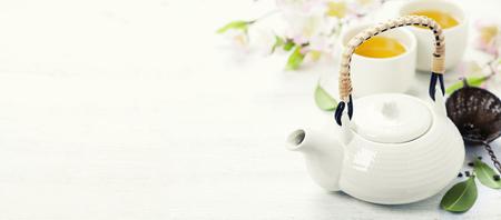 Conjunto de té chino y la rama de sakura en estera de bambú Foto de archivo - 46498346