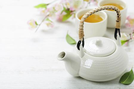 Conjunto de té chino y la rama de sakura en estera de bambú Foto de archivo - 46498358