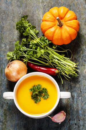 pumpkin soup: Pumpkin soup  with fresh ingredients on wooden board